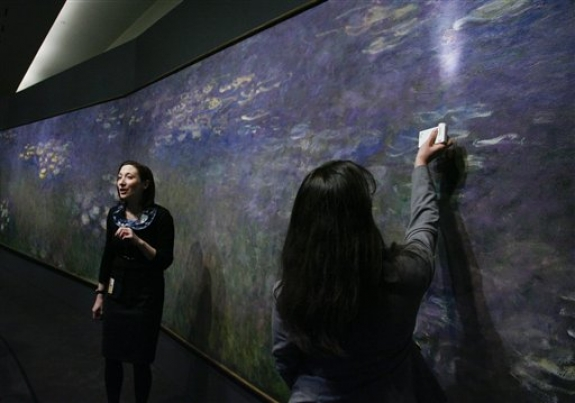 "Nicole Myers, Associate Curator of European Painting and Sculpture at the Nelson-Atkins Museum of Art, left, talks about Claude Monet's painting technique used on his painting ""Water Lilies"" as Mary Schafer, associate conservator, shines a light on a section of the work during a media preview, Friday, April 1, 2011, in Kansas City, Mo. For the first time in 30 years, the three panel work of the Impressionist artist will be on display at the museum and will run from April 9 through Aug. 7, 2011."