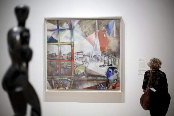 "A visitor views the exhibit ""Paris Through the Window: Marc Chagall and His Circle,"" including Chagall's painting, ""Paris Through the Window,"" at the Philadelphia Museum of Modern Art."