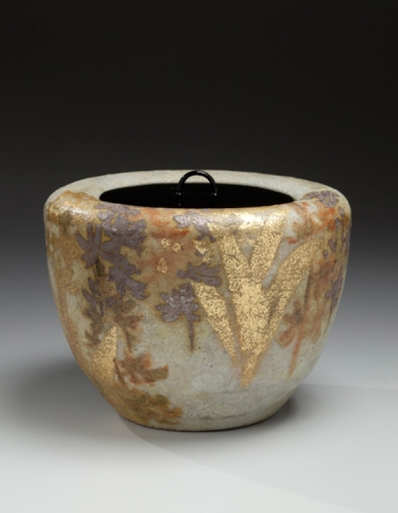 Kiyomizu Rokubei VI (1901-1980). Mizusashi (water jar) with floral patterning of an ebine (calanthe orchid) and lacquer lid. Japan, circa 1978. Kokisai-glazed stoneware with gold and silver. 6.38 x 8.5 inches (16.2 x 21.6 cm).