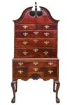 An early Chippendale bonnet top highboy of striking Cuban mahogany with claw and ball feet and Newport shell, original finial, c. 1765. Provenance with Olney family of Providence/Newport. Attribution: John Goddard, based upon the John Brown chair sold at Christie's, January 2002, lot 351, related claw and ball feet modeling. Courtesy of The Stanley Weiss Collection.