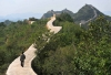 A villager walks across a restored section of the Great Wall in Suizhong County in northeastern China's Liaoning Province, on Wednesday, Sept. 21, 2016.